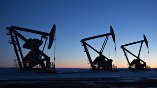 The silhouettes of pumpjacks are seen above oil wells in the Bakken Formation