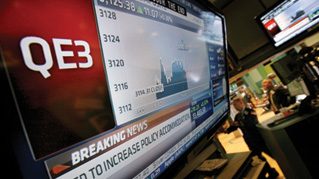 The rate decision of the Federal Reserve is announced on a television screen on the floor of the New York Stock Exchange