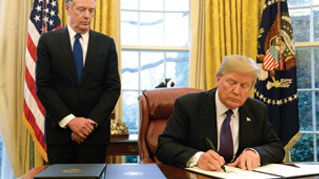 U.S. President Donald Trump signs Section 201 actions next to Bob Lighthizer, U.S. trade representative, left, in the Oval Office of the White House in Washington, D.C., U.S., on Tuesday, Jan. 23, 2018.