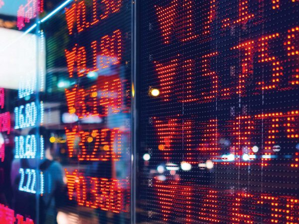 A close-up image of a stock exchange ticker display showing stocks plummeting in red.