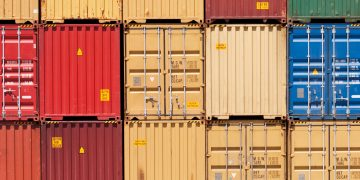 Image of shipping containers in rows and stacked on top of one another.