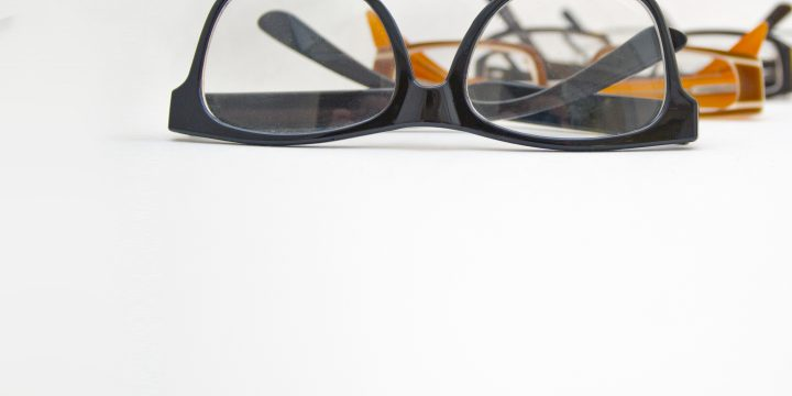 A photo zoomed in on a pair of eyeglasses in a row of other eyeglasses fading into the background.