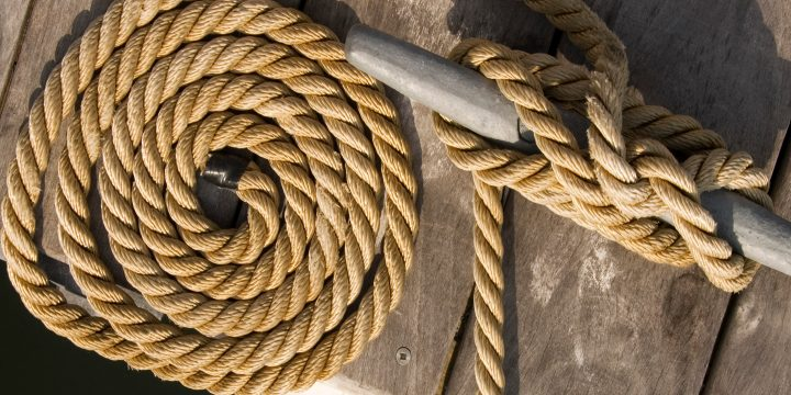 Stock photograph of rope on a dock's floor.