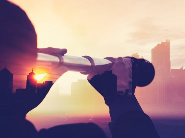 Person using a handheld telescope to view into a city off in the distance.