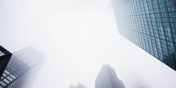 A low angle image of skyscrapers in Manhattan fading into the fog.