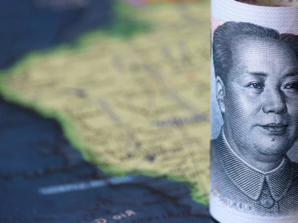 A rolled-up Chinese yuan on a map of South America