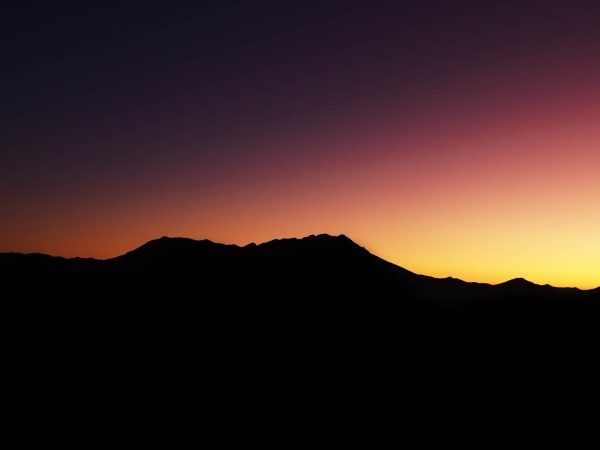 The silhouette of a mountain range against the backdrop of a lustrous red-yellow sunset.