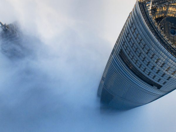 Image of the tops of 2 tall building poking through the clouds