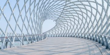 A close-up view of a futuristic pedestrian bridge with a metal crisscross tunnel-archway against the backdrop of a blue sky.