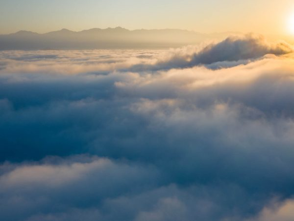 An aerial view of a sunrise over cloud tops.