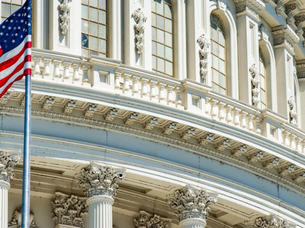 A close-up image of the Capitol dome in Washington, DC with an American flag waving off to the side.