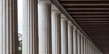 A close-up view of the top half of a line of classical, ancient Greek columns.