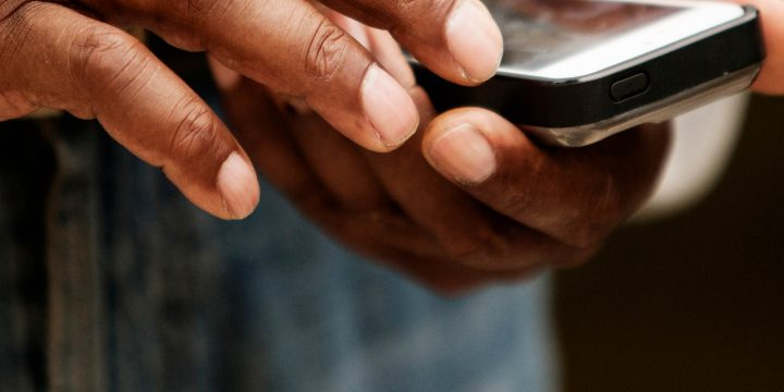Close-up shot of man's hands typing on phone.