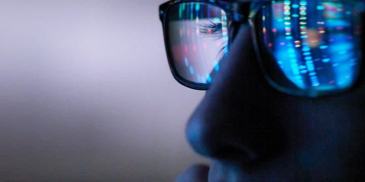 A close-up view of an eye glass reflecting the image of colorful patterns on a computer screen.