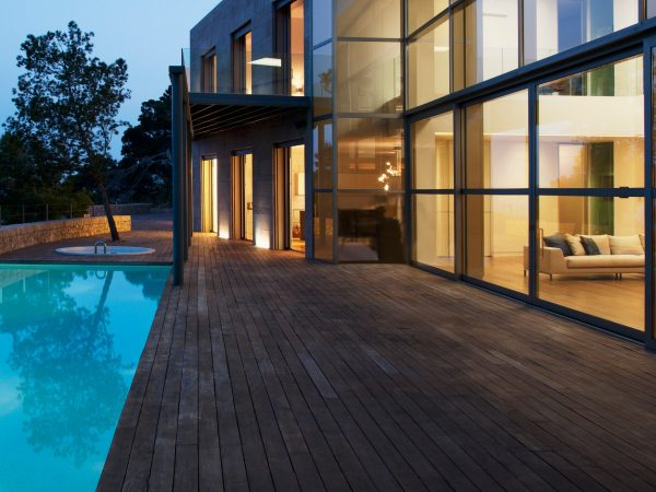 An infinity pool outside a modern house at twilight.