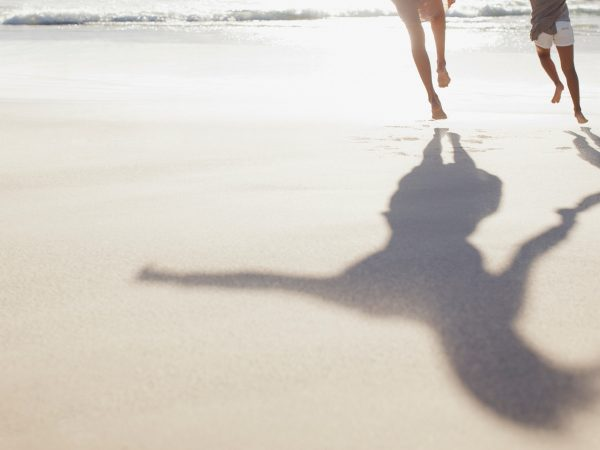 Image of parent and child from the waist down running on the beach with their full body shadows.