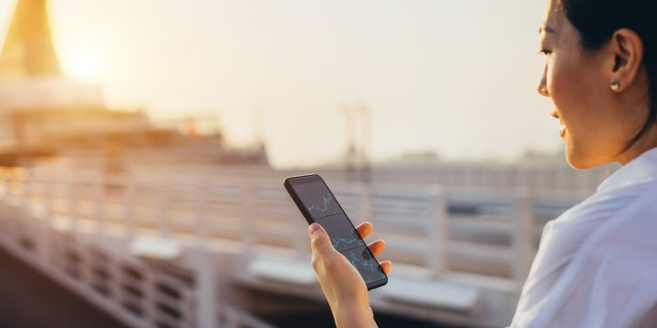 A businesswoman checking financial data on a smartphone in a commercial dock in a city at sunset.