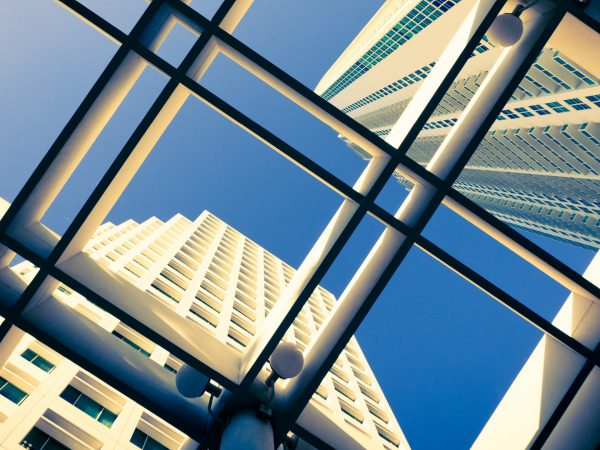 A low-angle view, through a glass rooftop with square metal beams, of skyscrapers protruding upward.