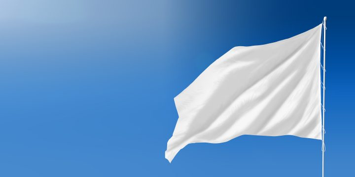A white flag waving against a clear blue sky.