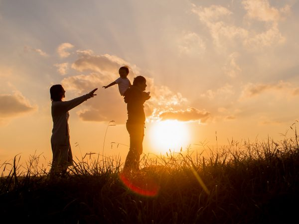 Image of a woman and a man carrying a child during sunset