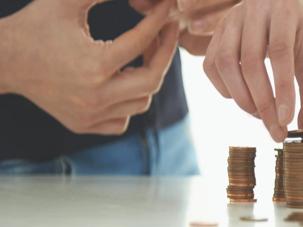 Two people stacking coins.