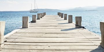 An empty pier stretching out over the water with a sailboat and mountains in the backdrop.