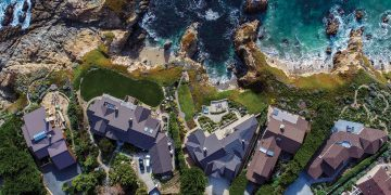 An aerial image of houses along a rocky coastline